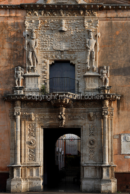 Detail of entrance to La Casa de Montejo (Montejo's House), 1549 Merida, Yucatan, Mexico, pictured on July 13, 2006, in the evening. In 1542 Spanish Conquistadors, led by Francisco de Montejo (the Younger) captured the ancient Mayan city of Th'o, and built a new city named after Merida in Spain. The two tiers of the sculpted facade of Montejo's house illustrate the characteristics of Plateresque architecture, a combination of late Gothic, Moorish and early Renaissance styles. The lower facade features fluted columns, classical entablatures and coffered panelling in Renaissance style. The two busts above the doorway are thought to be Montejo's parents. The upper tier suggesting the Medieval and Moorish has a frieze of grotesques and a bowed figure supporting the corbelled balcony. Above the window is the Montejo shield. Huge figures of Spanish halbardiers stand on heads, often interpreted as Mayans, but probably European demons. Picture by Manuel Cohen.