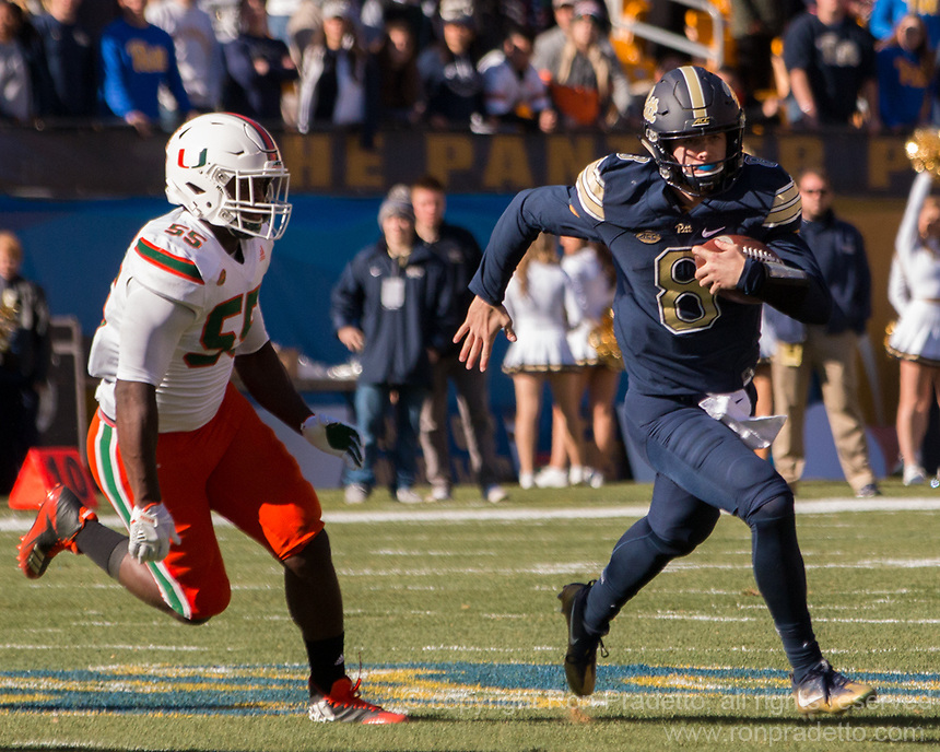 Pitt quarterback Kenny Pickett escapes Miami linebacker Shaquille Quarterman. The Pitt Panthers upset the undefeated Miami Hurricanes 24-14 on November 24, 2017 at Heinz Field, Pittsburgh, Pennsylvania.