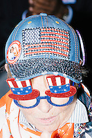 A woman wears a bedazzled patriotic hat and glasses while sitting in the delegate area during a speech at the Democratic National Convention at the Wells Fargo Center in Philadelphia, Pennsylvania, on Wed., July 27, 2016.