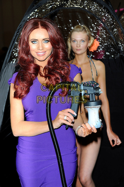 Amy Childs.Amy Childs photocall before (Failed)  Guinness World Record Attempt of the most people being spray tanned at the same time at the Professional Beauty Show, Excel, London, England..February 25th, 2013.half length purple dress bottle hose tent.CAP/CJ.©Chris Joseph/Capital Pictures.