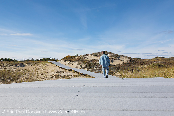 Man walking on boardwalk at Parker River National Wildlife Refuge on Plum Island, Massachusetts during the autumn months.