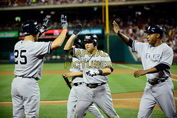 New York Yankees first baseman Mark Teixeira (25), left, congratulates teammates Russell Martin (55), center, and Dewayne Wise (45) after they scored on a Derek Jeter single and a throwing error by Washington Nationals shortstop Ian Desmond in the seventh inning at Nationals Park in Washington, D.C. on Friday, June 15, 2012.  The Yankees won the game 7 - 2.  .sport athlete baseball half length grey gray uniform hands high five arms in air cap hat.CAP/ADM/RS.©Ron Sachs/CNP/AdMedia/Capital Pictures.