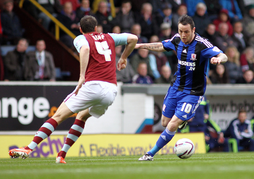 Middlesbrough&rsquo;s Lee Tomlin looks to pass Burnley's Michael Duff <br /> <br /> Photo by Rich Linley/CameraSport<br /> <br /> Football - The Football League Sky Bet Championship - Burnley v Middlesbrough - Saturday 12th April 2014 - Turf Moor - Burnley<br /> <br /> &copy; CameraSport - 43 Linden Ave. Countesthorpe. Leicester. England. LE8 5PG - Tel: +44 (0) 116 277 4147 - admin@camerasport.com - www.camerasport.com