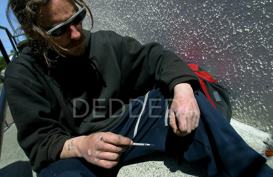 An IV drug user holds a needle after injecting morphine into his arm in Victoria, BC, British Columbia, Canada.  He is sitting in an area between two buildings which is a common site for intravenous drug users to utilize as a shooting gallery. Photo shot for the GLOBE and MAIL.