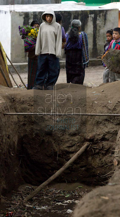 People visit graves, and a trench to hold the bodies in new graves, of Panabaj, Guatemala townspeople, killed in a massive mudslide on October 5, at the cemetery in nearby Santiago Atitlán, Guatemala on Tuesday, Nov. 1, 2005, part of the traditional Day of the Dead. Torrential rains and mudslides associated with Hurricane Stan devasted some parts of western Guatemala in early October. The Guatemalan government has put the number of dead at 669, and says that 31, 971 people are living in shelters. Locals say at least 500 people were killed at Panabaj.