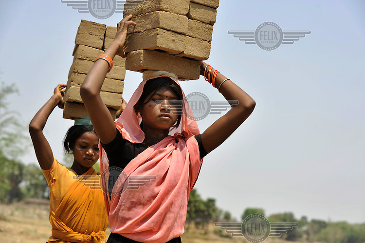 Young girls carry bricks on their heads at the local brick kiln in Jalhe Bhongia Village.