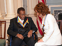 Wayne Shorter, left and Reba McEntire, right, two of the recipients of the 41st Annual Kennedy Center Honors, converse prior to posing for a group photo following a dinner hosted by United States Deputy Secretary of State John J. Sullivan in their honor at the US Department of State in Washington, D.C. on Saturday, December 1, 2018.  The 2018 honorees are: singer and actress Cher; composer and pianist Philip Glass; Country music entertainer Reba McEntire; and jazz saxophonist and composer Wayne Shorter. This year, the co-creators of Hamilton, writer and actor Lin-Manuel Miranda; director Thomas Kail; choreographer Andy Blankenbuehler; and music director Alex Lacamoire will receive a unique Kennedy Center Honors as trailblazing creators of a transformative work that defies category.<br /> CAP/MPI/RS<br /> &copy;RS/MPI/Capital Pictures