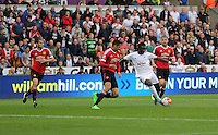 Pictured: Bafetimbi Gomis of Swansea (3rd L) marked closely by Chris Smalling of Manchester United, takes a shot a few inches away from the post Sunday 30 August 2015<br />