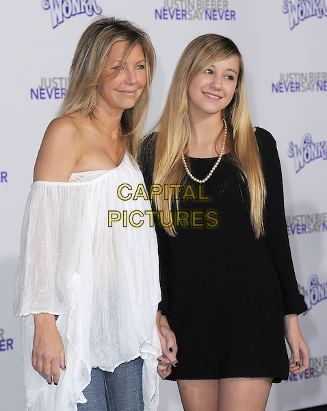 "HEATHER LOCKLEAR & AVA SAMBORA .attending the Paramount Pictures' L.A. Premiere of ""Justin Bieber: Never Say Never"" held at The Nokia Theater Live in Los Angeles, California, USA,.February 8th 2011..half length mother mum mom daughter black dress holding hands family off the shoulder poncho white top                                  .CAP/RKE/DVS.©DVS/RockinExposures/Capital Pictures."