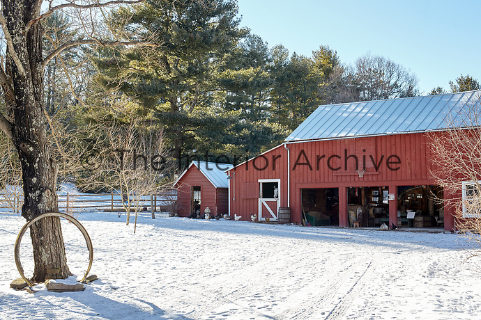 The oxblood red-painted exterior of the refurbished barn stands out against its snowy surroundings