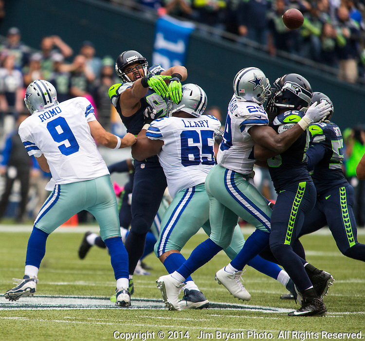 Dallas Cowboys quarterback Tony Romo (9) passes under pressure from Seattle Seahawks  defensive tackle Jordan Hill (97) at CenturyLink Field in Seattle, Washington on October 12, 2014. The Cowboys beat the Seahawks 30-23 .  ©2014. Jim Bryant Photo. All rights Reserved.
