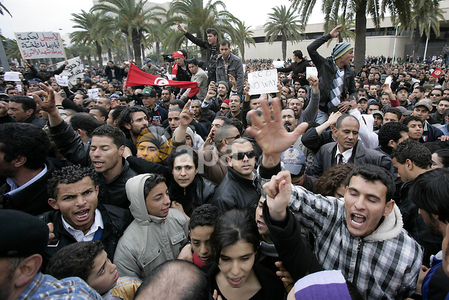 Tunisians take part in a protest in front of the headquarters of the Constitutional Democratic Rally (RCD) party of ousted president Zine al-Abidine Ben Ali during a demonstration in downtown Tunis, January 20, 2011. Tunisian police fired shots into the air on Thursday to try to disperse hundreds of protesters demanding that ministers associated with the rule of ousted president Zine al-Abidine Ben Ali leave the government. The protesters, who had gathered outside the central Tunis headquarters of the RCD, Tunisia's ruling party for several decades, refused to move back when the police fired shots from behind a metal fence. Photo by STR