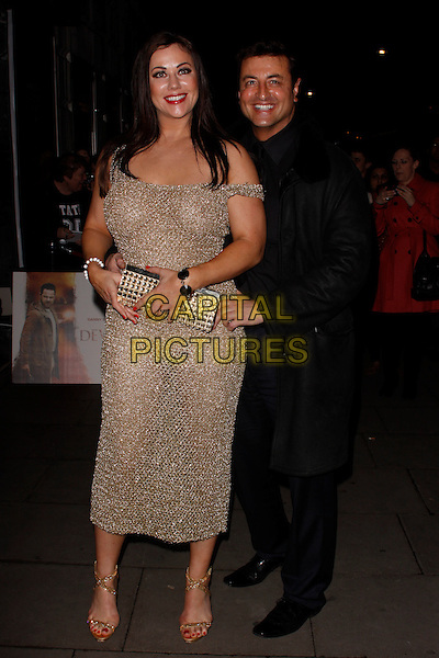 Lisa Appleton & Mario Marconi.The 'Deviation' UK film premiere, Odeon Covent Garden cinema, Shaftesbury Avenue, London, England..February 23rd, 2012.full length gold dress off the shoulder see through thru nipple clutch bag hand on hip black coat couple arms around waist .CAP/AH.©Adam Houghton/Capital Pictures.