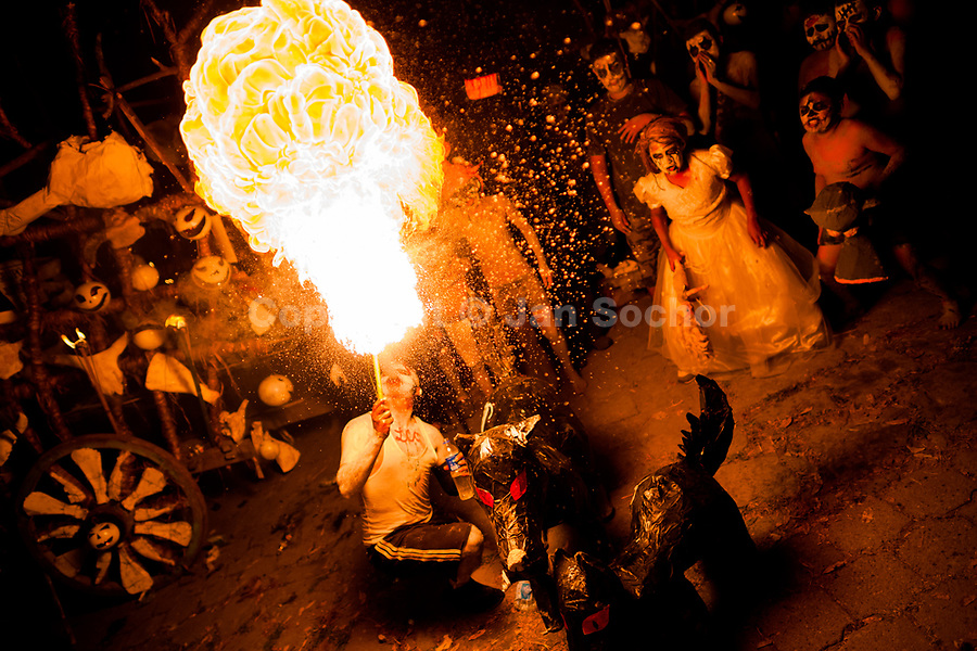 A young Salvadoran man spits fire as he performs during the La Calabiuza parade at the Day of the dead festivity in Tonacatepeque, El Salvador, 1 November 2016. The festival, known as La Calabiuza since the 90s of the last century, joins Salvador's pre-Hispanic heritage and the mythological figures (La Sihuanaba, El Cipitío, La Llorona etc.) collected from the whole Central American region, together with the catholic All Saints Day holiday and its tradition of honoring the dead relatives. Children and youths only, dressed up in scary costumes and carrying painted carts, march from the local cemetery to the downtown plaza where the party culminates with music, dance, drinking and eating pumpkin (Ayote) with honey.