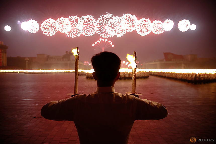 Fireworks explode over participants carrying torches during a torchlight procession in the capital's main ceremonial square, a day after the ruling Workers' Party of Korea party wrapped up its first congress in 36 years, in Pyongyang, North Korea May 10, 2016.  REUTERS/Damir Sagolj