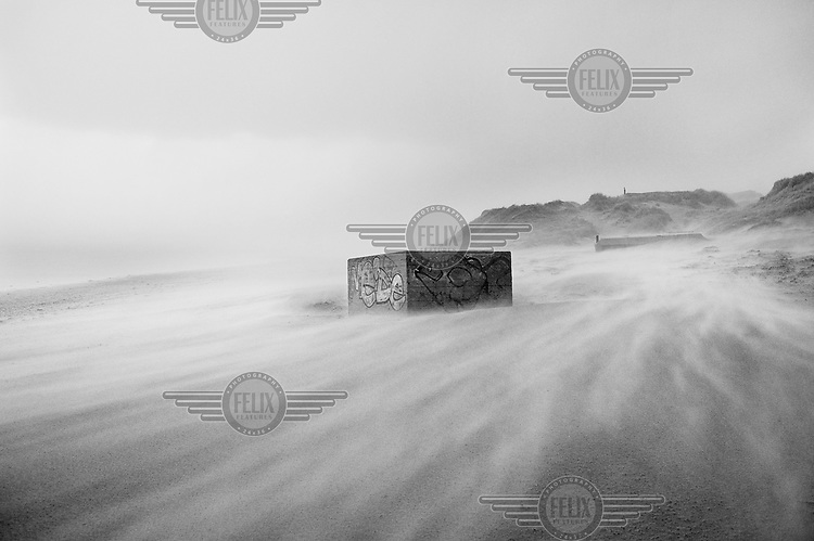 A former defensive bunker, covered in graffiti, stands on a wind swept beach in Berck, France, along the route of the Atlantic Wall (Atlantikwall in German).The Atlantic Wall (or Atlantikwall in German) was a system of defensive structures built by Nazi Germany between 1942 and 1945, stretching over 1,670 miles (2,690 km) along the coast from the North of Norway to the border between France and Spain at the Pyrenees. The wall was intended to repulse an Allied attack on Nazi-occupied Europe and the largest concentration of structures was along the French coast since an invasion from Great Britain was assumed to be most likely. Slave labour and locals paid a minimum wage were drafted in to supply much of the labour. There are still thousands of ruined structures along the Atlantic coast in all countries where the wall stood except for Germany, where the bunkers were completely dismantled.