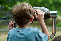 Boy looking through a viewing scope.