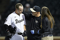 Wake Forest Demon Deacons trainer Jeff Strahm (center) checks on catcher Brendan Tinsman (9) after he was hit in the head by a pitch while batting against the Sacred Heart Pioneers at David F. Couch Ballpark on February 15, 2019 in  Winston-Salem, North Carolina.  The Demon Deacons defeated the Pioneers 14-1.  (Brian Westerholt/Four Seam Images)