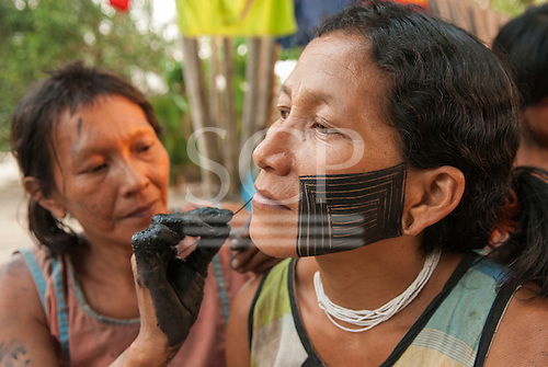 Aldeia Baú, Para State, Brazil. One woman painting another's with genipapu face paint.