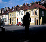Elderly man with walking sticks silhouetted against a row of wooden fronted houses in Bergen, Norway.