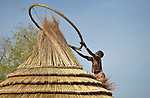 Aloel Dau works on the thatched roof of her hut in a displaced persons camp in Agok, South Sudan. Tens of thousands of residents of Abyei, a contested region along the border between Sudan and South Sudan, remain displaced in Agok. Under a 2005 peace agreement, Abyei was supposed to have a referendum to decide which country it would join, but the two countries have yet to agree on who can vote. In 2011, militias aligned with Khartoum drove out most of Abyei's Dinka Ngok residents, pushing them across a river into the town of Agok. More than 40,000 Dinka Ngok have since returned to Abyei with support from Caritas South Sudan, which has drilled wells, built houses, opened clinics and provided seeds and tools for the returnees. Yet continuing insecurity means a greater number remain in Agok, where they remain dependant on Caritas and other organizations for food and other support.