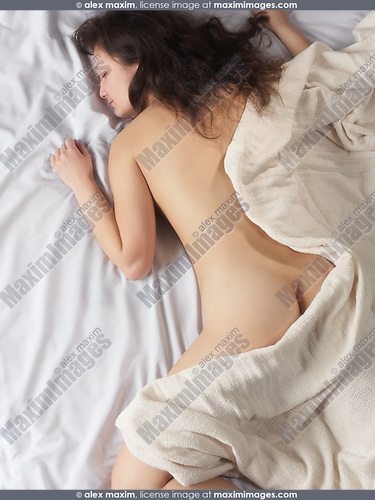 High angle view of a young woman sleeping in bed naked