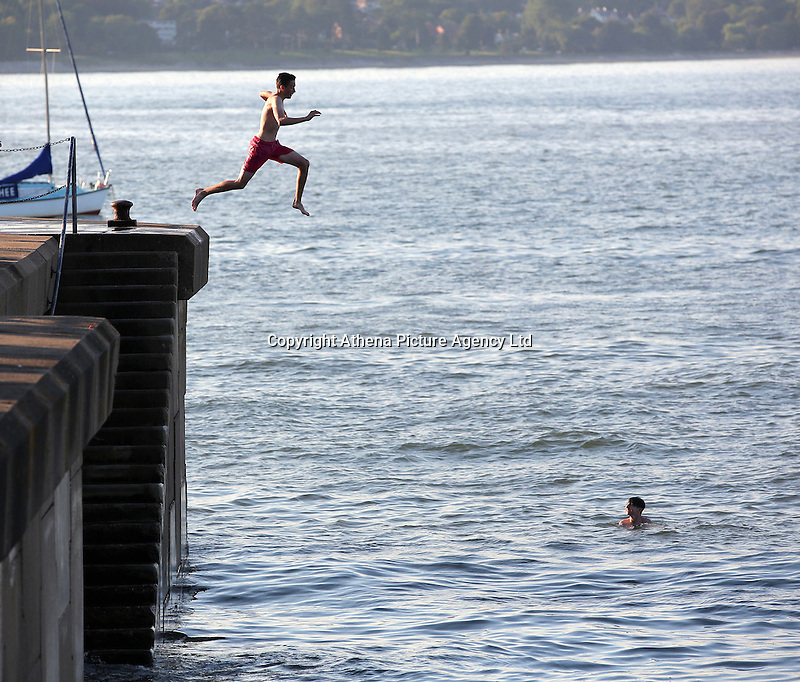 WEATHER PICTURE WALES<br />Pictured: A boy jumps off the promenade wall in Mumbles, south Wales UK. Tuesday 16 August 2016<br />Re: High temperatures and sunshine experienced in most of the UK.