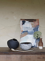 Still life shows objects atop a wooden surface, in front of a cracked, beige, stone wall. In the foreground is a wooden spoon, lying length-ways on the wooden surface, with it's head facing the left. The spoon has a painted, decorative, dark handle. Behind the spoon are two vases. One black and the other white, with a cracked-paint effect applied. To the right of these there is another vase. This one has been painted, the top half brown and the bottom white. There is a small bunch of flowers in the vase. Behind the flowers, propped against the stone wall, is a canvas with paint stripes of blue, white, black, red and brown. The artwork was done by Jacqui Rufus Isaacs. The photograph was taken straight on to the wall, eye level to the canvas.