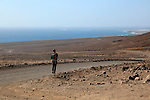 Lone man walking in barren landscape Jandia peninsula, Fuerteventura, Canary Islands, Spain