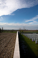 The New British Cemetery at Passendale and a ploughed field abutting it. Nearly one hundred years after WWI farmers are still revealing ordnance when they plough their fields.