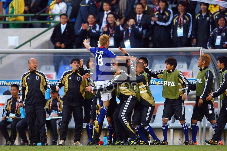 Keisuke Honda (centre) of Japan celebrates his goal against Cameroon