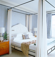 The master bedroom is furnished with a contemporary wrought iron four-poster bed draped with white hangings