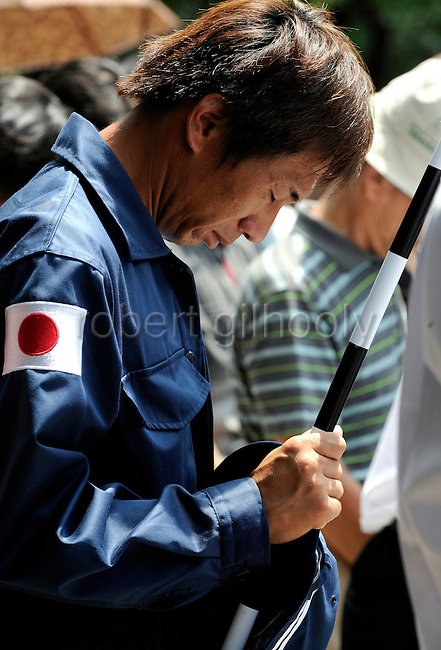 A Japanese nationalist man bows in prayer during a minute's silence held to commemorate the end of World War II at Yasukuni Shrine in Tokyo, Japan on 15 Aug. 2008. Wartime prime minister Hideki Tojo - who ordered the attack on Peal Harbor and was charged and hanged as a war criminal after World War II, is enshrined inside the controversial Yasukuni Shrine together with 13 other convicted war criminals, a fact that still angers citizens in China and South Korea, both of which fell vicim to Japan's wartime activities. Aug 15. is the anniversary of Japan's surrender in World War II and 100s of thousands of pilgrims from around the country visit the shrine..Photographer: Robert Gilhooly