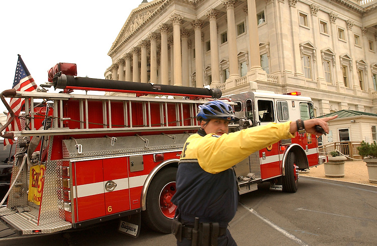A Capitol Police officer directs foot traffic off the Senate Side of the Capitol, Monday.   DCFD arrived to find smoke in the basement that was drawn in from the construction outside.   There was no fire.