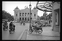 Vietnamese commuters pass by the Hanoi Opera House in the French section of Hanoi, Vietnam, June 2016.