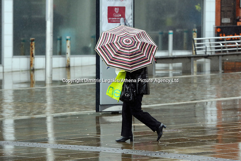 WEATHER PICTURE WALES<br /> Pictured: A woman with an umbrella walks in Oxford Street, Swansea, south Wales. Friday 14 February 2014<br /> Re: More strong winds have been forecast and severe flood warning issued for parts of the UK.