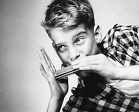 Young boy playing the harmonica.