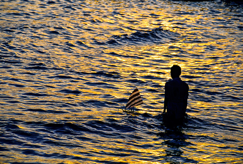 Boy with toy sailboat at sunset, Candi Dasa Beach, Bali, Indonesia
