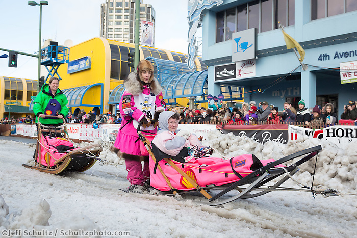 DeeDee Jonrowe and team leave the ceremonial start line with an Iditarider at 4th Avenue and D street in downtown Anchorage, Alaska during the 2015 Iditarod race. Photo by Jim Kohl/IditarodPhotos.com