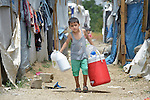 A boy carries water containers through in a settlement of Syrian refugees in Minyara, a village in the Akkar district of northern Lebanon. Lebanon hosts some 1.5 million refugees from Syria, yet allows no large camps to be established. So refugees have moved into poor neighborhoods or established small informal settlements in border areas. International Orthodox Christian Charities, a member of the ACT Alliance, provides a variety of support for families in this settlement, including some meals prepared in a community kitchen.