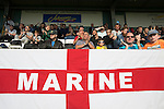 Home supporters watching the second-half action at the Mersey Travel Arena, home to Marine Football Club (in white), as they played host to Ilkeston FC in a Northern Premier League premier division match. The match was won by the home side by 3 goals to 1 and was watched by a crowd of 398. Marine are baed in Crosby, Merseyside and have played at Rossett Park (now the Mersey Travel Arena)  since 1903, the club having been formed in 1894.