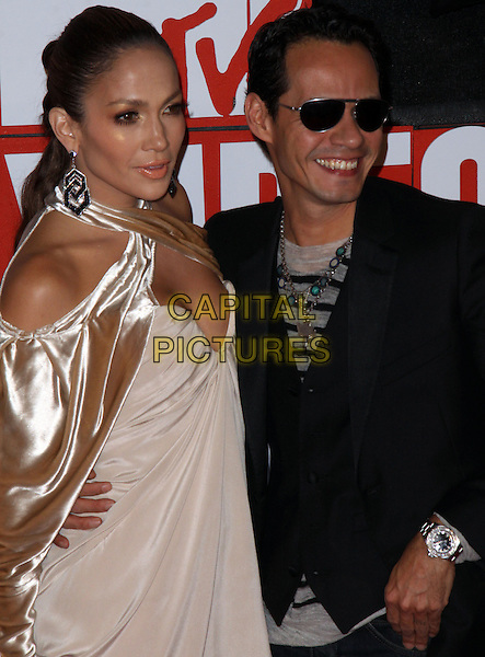 JENNIFER LOPEZ & MARC ANTHONY .2009 MTV Video Music Awards arrivals held at Radio City Music Hall, New York, NY, USA..September 13th, 2009.half length black suit jacket sunglasses shades beige gold dress velvet sleeves clutch bag halterneck wrap married husband wife.CAP/ADM/PZ.©Paul Zimmerman/AdMedia/Capital Pictures.