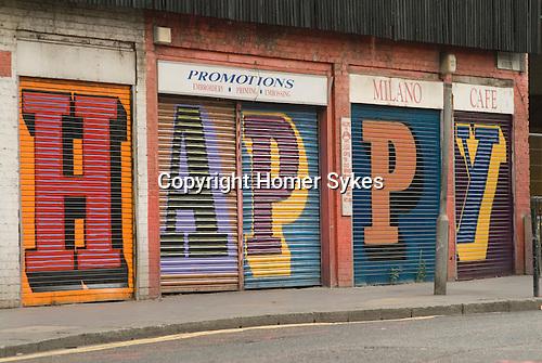 "Middlesex Street East End London E1. Alphabet Street project ""HAPPY"" on shop shutters work by street artist Ben Eine (real name Ben Flynn)."
