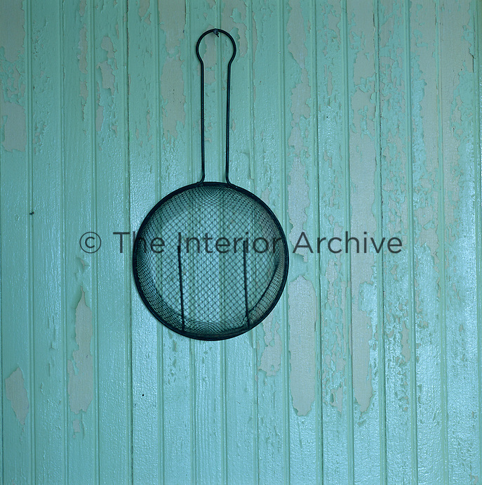 A simple nail in a wall of painted tongue and groove provides a hook for an old-fashioned sieve