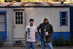 "Daniel Hurt, left, and Otis Coots stand outside of Coots' small apartment on the side of Highway 421.  Coots is unable to work due to a severe back injury and cares for his father, who has Alzheimer's and also lives in the group of apartments.  Hurt called the group of apartments the ""projects of Hyden.""  Photo by Morgan Eads"