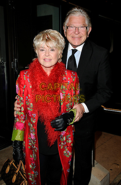 "GLORIA HUNNIFORD & STEPHEN WAY.Attending ""Still Missing, Still MIssed"" Fundraiser to mark the 1000th day since the disappearance of Madeline McCann, The Roof Gardens, Kensington High Street, London, England, UK, .January 27th 2010..half  length red feather boa scarf fluffy black gloves tie coat glasses green pattern print pink floral husband wife couple married .CAP/CAN.©Can Nguyen/Capital Pictures."