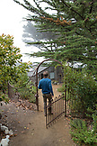 USA, California, Big Sur, Esalen, a man walks through a gate to the Point Houses at the Esalen Institute