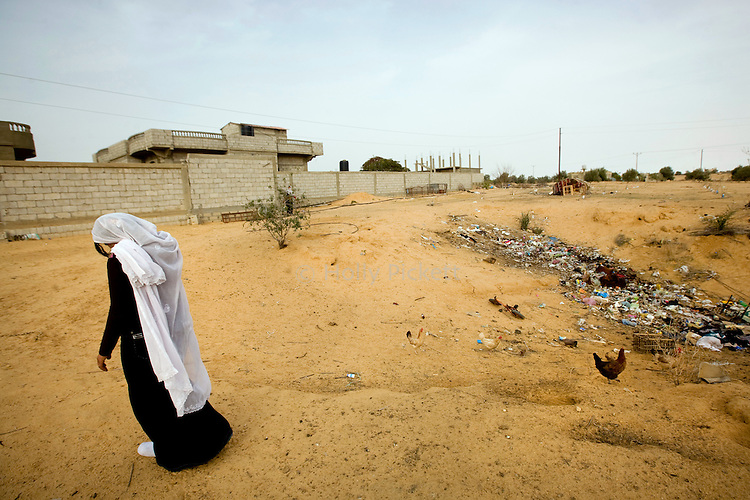 A Bedouin woman walks near her home in the Sinai peninsula, near the border with Gaza, Jan. 28, 2010. She is married to a Bedouin who makes his living smuggling goods and humans from Egypt across the Gaza and Israel borders. A barrier wall being built buy Egypt may impact the illegal trade, causing strife between the government and Egypt's marginalized Bedouin tribes.