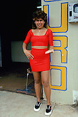 "Porto Velho, Brazil. ""Working girl"" wearing skin tight bright red skirt and top showing her earnings in gold outside a gold dealer."