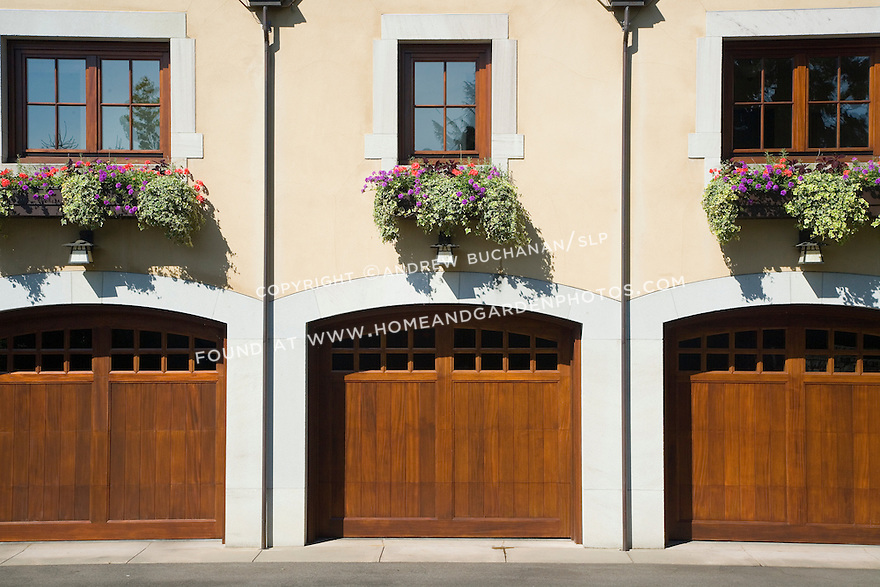 detail of a stucco-sided garage and upper living quarters sporting symmetrical window boxes above identical wooden carriage house style garage doors